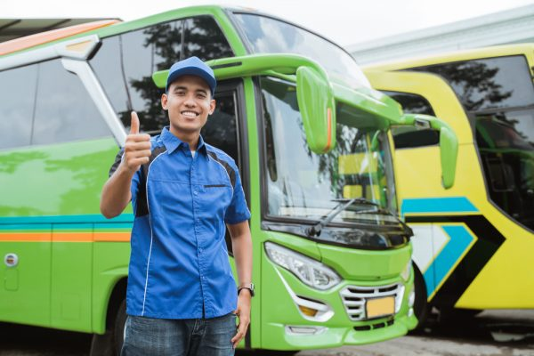 Seorang sopir bus berseragam dan bertopi tersenyum sambil mengacungkan jempol di latar belakang bus