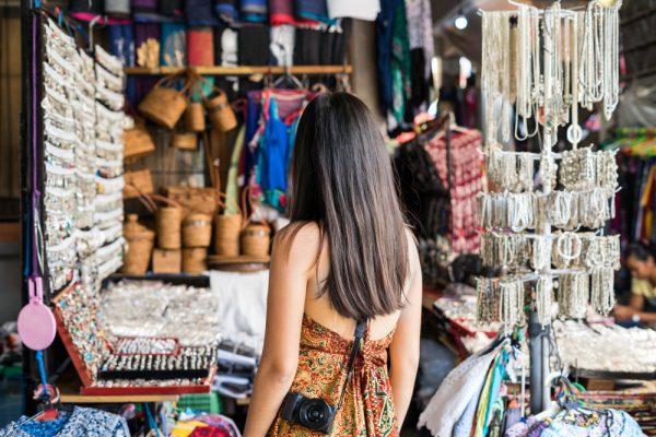 Pelancong wanita muda mencari suvenir di pasar ubud di bali