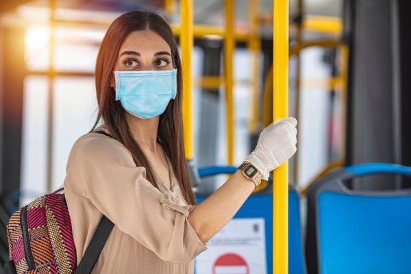 Seorang wanita muda di angkutan umum selama pandemi.